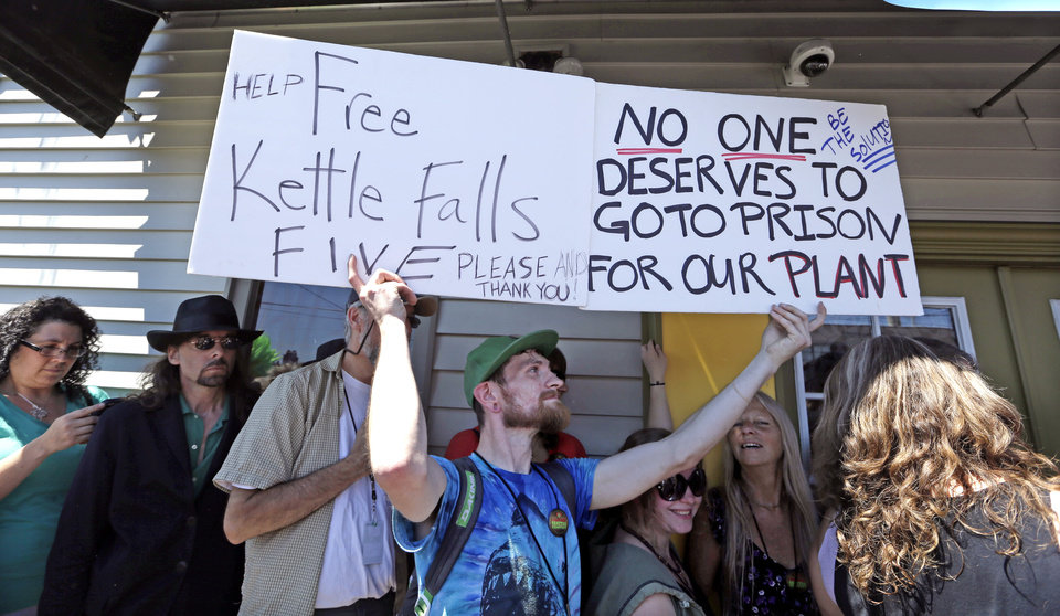 Photo - Jacob Junkman holds up signs as he waits in line at Cannabis City on the first day that sales of recreational pot became legal in the state Tuesday, July 8, 2014, in Seattle. Washington on Tuesday became the second state to allow people to buy marijuana legally in the U.S. without a doctor's note as eager customers who lined up outside stores made their purchases and savored the moment. (AP Photo/Elaine Thompson)