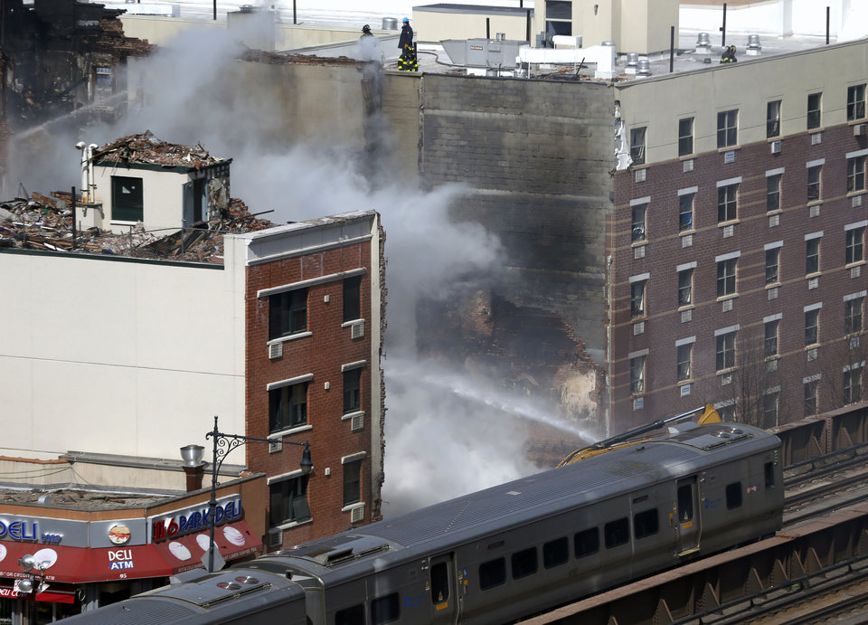Photo - A Metro-North commuter train goes by the site where a gas leak-triggered explosion occurred the day before, Thursday, March 13, 2014, in East Harlem, New York. Rescuers working amid gusty winds, cold temperatures and billowing smoke pulled additional bodies Thursday from the rubble of two apartment buildings that collapsed Wednesday. (AP Photo/Julio Cortez)