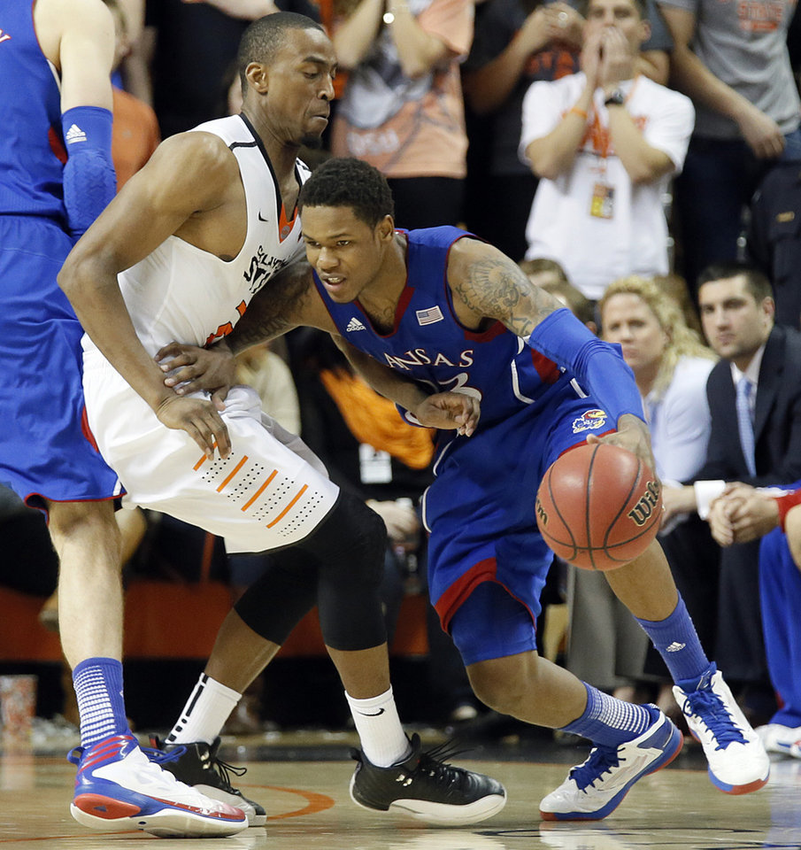 Photo - Oklahoma State 's Markel Brown (22) defends on Kansas' Ben McLemore (23) during the college basketball game between the Oklahoma State University Cowboys (OSU) and the University of Kanas Jayhawks (KU) at Gallagher-Iba Arena on Wednesday, Feb. 20, 2013, in Stillwater, Okla. Photo by Chris Landsberger, The Oklahoman