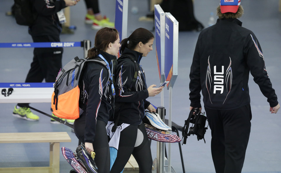 Photo - U.S. speedskaters Heather richardson, left, and Brittany Bowe hold their skates and walk out of the arena after competing in the women's team pursuit race to take sixth place against Canada at the Adler Arena Skating Center at the 2014 Winter Olympics, Saturday, Feb. 22, 2014, in Sochi, Russia. (AP Photo/Matt Dunham)