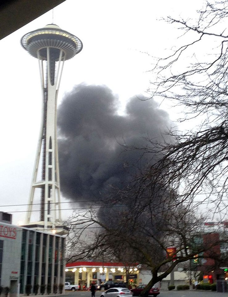 Photo - In this photo provided by KIRO- TV,  smoke rises at the scene of a news helicopter crash outside the KOMO-TV studios near the space needle in Seattle on Tuesday, March 18, 2014. The chopper was taking off from a helipad on KOMO-TV's roof when it went down at a busy downtown intersection and hit three vehicles, starting them on fire and spewing burning fuel down the street. Two people on board the helicopter died. (AP Photo/KIRO-TV)