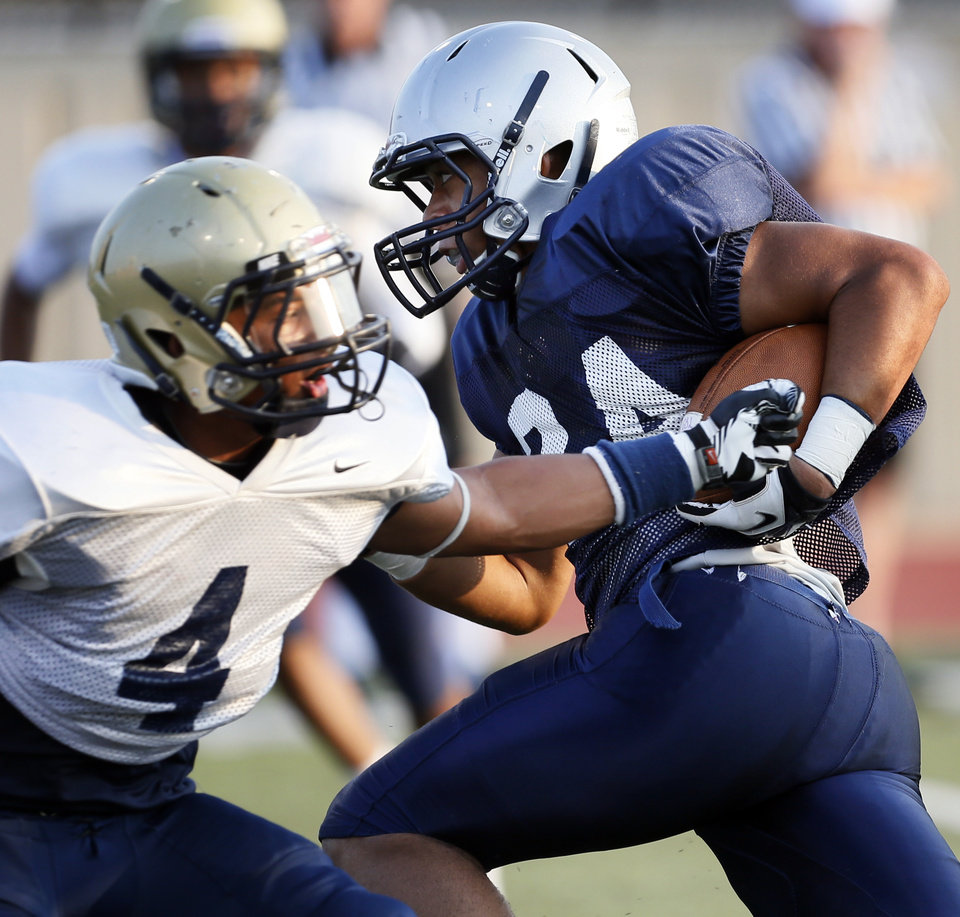 Edmond North's Ezel McIntee (24) avoids Southmoore's Johnathan Martin (4) during a high school football scrimmage at Moore Stadium in Moore, Okla., Friday, Aug. 17, 2012. Photo by Nate Billings, The Oklahoman