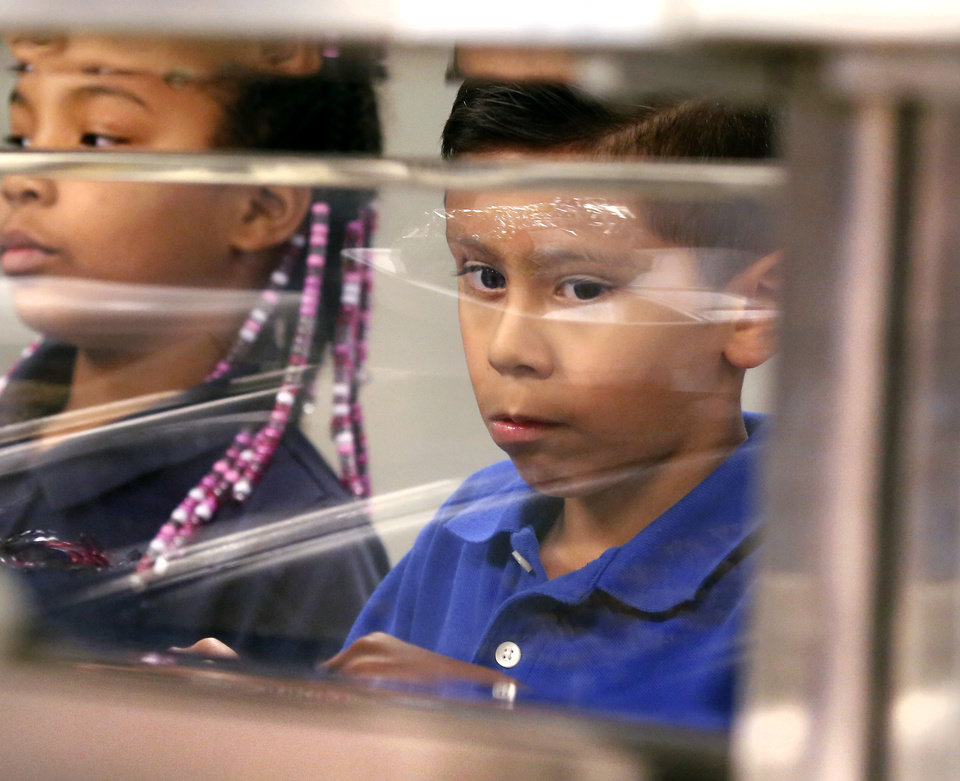 Photo -  Students peer through the glass to see what they are getting for lunch Thursday at Eugene Field Elementary School. [Photo by Jim Beckel, The Oklahoman]