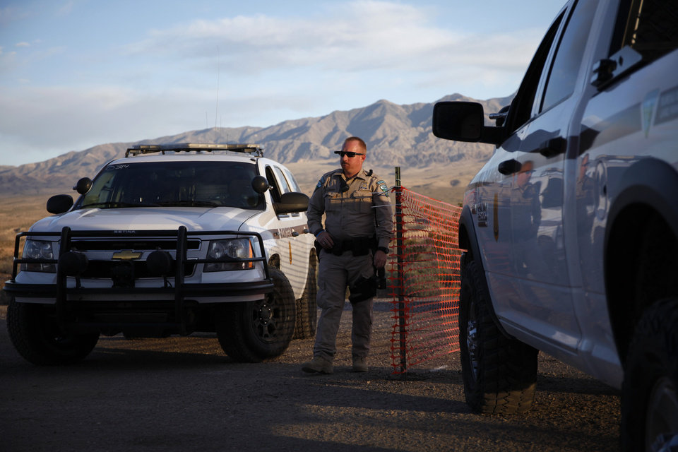 Photo - A Bureau of Land Management ranger stands guard at the entrance of a staging area near Mesquite, Nev. Saturday, April 5, 2014.  The U.S. Bureau of Land Management started taking cattle on Saturday from rancher Cliven Bundy, who it says has been trespassing on U.S. land without required grazing permits for over 25 years. Bundy doesn't recognize federal authority on land he insists belongs to Nevada. (AP Photo/Las Vegas Review-Journal, John Locher)