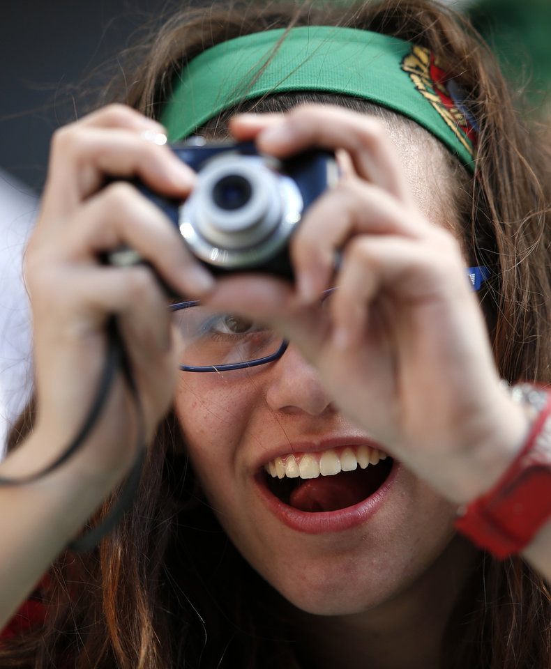 A Portuguese fan tries to take pictures of the players warming up during the Euro 2012 soccer championship Group B match between Denmark and Portugal in Lviv, Ukraine, Wednesday, June 13, 2012. (AP Photo/Armando Franca)