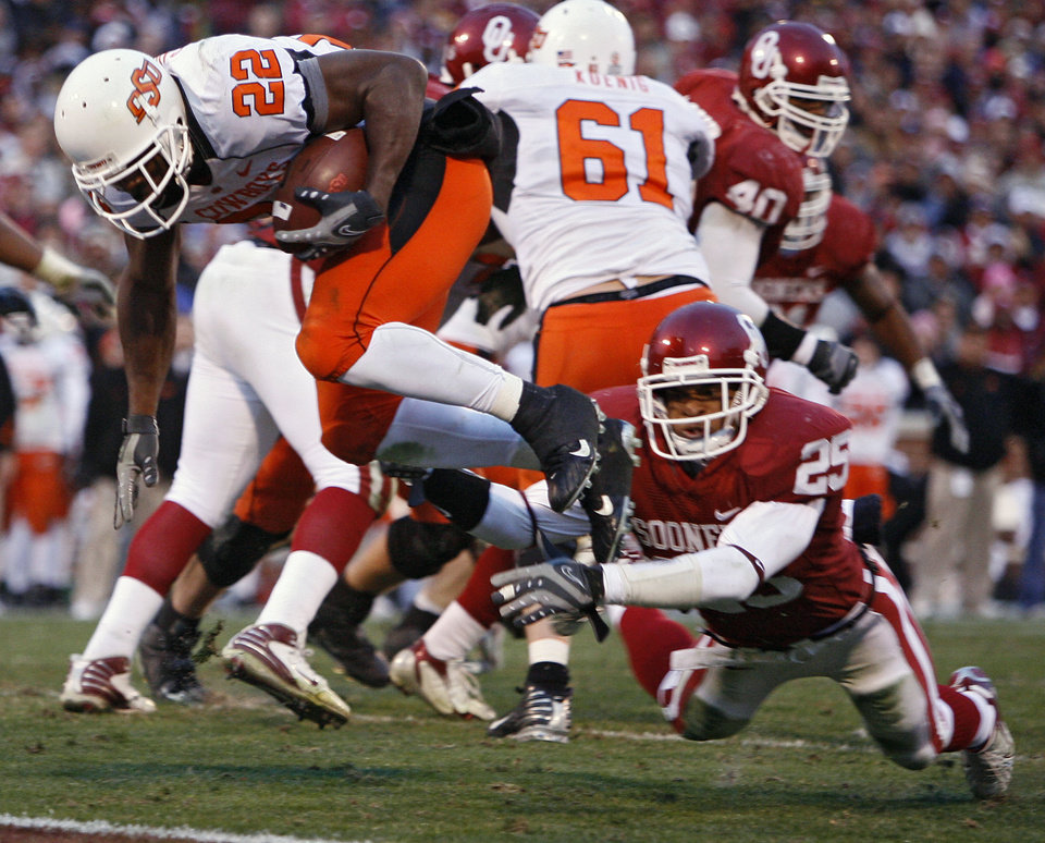 Photo - Oklahoma State's Dantrell Savage (22) dives past Oklahoma's D.J. Wolfe (25) to score a touchdown during the second half of the college football game between the University of Oklahoma Sooners (OU) and the Oklahoma State University Cowboys (OSU) at the Gaylord Family-Memorial Stadium on Saturday, Nov. 24, 2007, in Norman, Okla.  Photo By Bryan Terry, The Oklahoman
