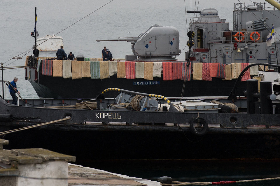 Photo - People work on board the Ukrainian navy corvette Ternopil, background, at harbor of  in Sevastopol, Ukraine, Tuesday, March 4, 2014. Crimea still remained a potential flashpoint. Pro-Russian troops who had taken control of the Belbek air base in Crimea fired warning shots into the air Tuesday as around 300 Ukrainian soldiers, who previously manned the airfield, demanded their jobs back. The blankets and mattresses are placed over the side of the ship to hinder any attempted assault. (AP Photo/Andrew Lubimov)