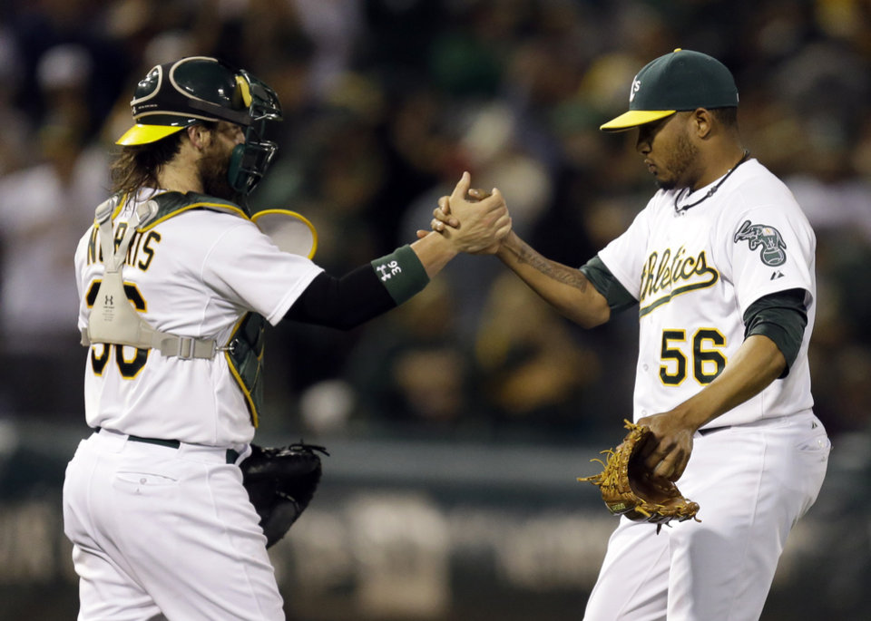 Photo - Oakland Athletics' Fernando Abad, right, celebrates with catcher Derek Norris after their 5-1 win in a baseball game against the Toronto Blue Jays Saturday, July 5, 2014, in Oakland, Calif. (AP Photo/Ben Margot)