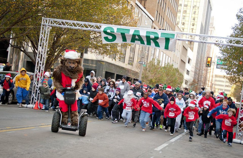 Photo - Rumble the Bison leads participants during the SandRidge Santa Run, part of Downtown in December. Photo provided.