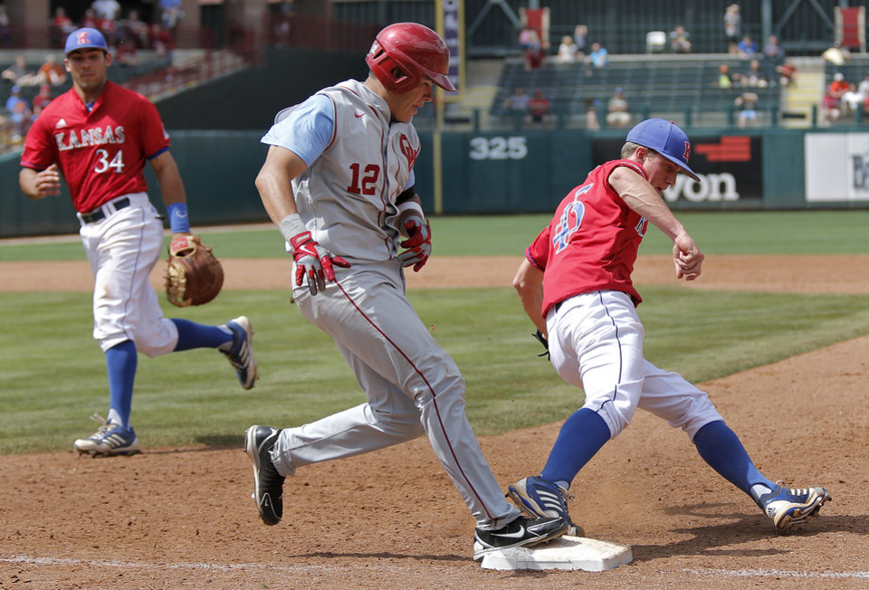 Oklahoma's Hector Lorenzana (12) is tagged out at first by Kansas' Jordan Piche' (45) in the Big 12 Championship baseball game between the University of Kansas Jayhawks (KU) and the University of Oklahoma Sooners (OU) at the Chickasaw Bircktown Ballpark on Sunday, May 26, 2013 in Oklahoma City, Okla.  Photo by Chris Landsberger, The Oklahoman