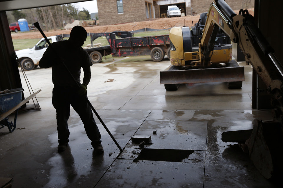 Photo - A worker breaks free concrete inside Patrick and Kim Lenow's home in preparation to install a storm shelter. Photo by Bryan Terry, The Oklahoman