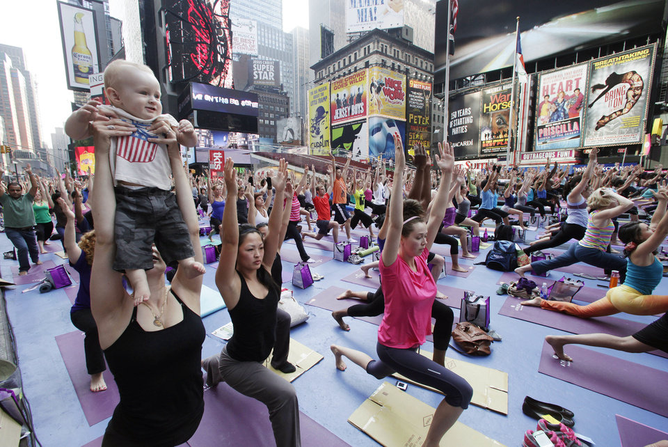 Photo - Yoga enthusiasts work out in hot weather in New York's Times Square.  (AP)  Mark Lennihan
