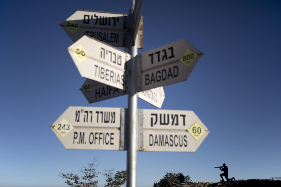 Photo - A sign showing the direction and distance to cities stands as a metal board in the shape of a gunman is placed on an old bunker at an observation point on Mt. Bental in the Israeli controlled Golan Heights, overlooking the border with Syria, Thursday, Aug. 28, 2014. (AP Photo/Ariel Schalit)