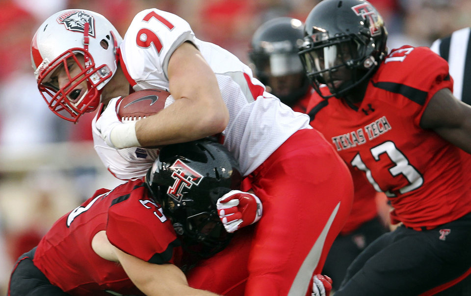 Photo -   FILE - In this Sept. 15, 2012, file photo, New Mexico's Lucas Reed is tackled by Texas Tech's Blake Dees (25) and Sam Eguavoen (13) during their NCAA college football game in Lubbock, Texas. Texas Tech has long been known for slinging passes all over the Big 12. No longer, at least through Texas Tech's first three games against non-conference opponents. The Red Raiders (3-0) are No. 2 in the nation in total defense (120 yards per game) and in passing defense (85 ypg).(AP Photo/The Avalanche-Journal, Stephen Spillman, File) ALL LOCAL TV OUT