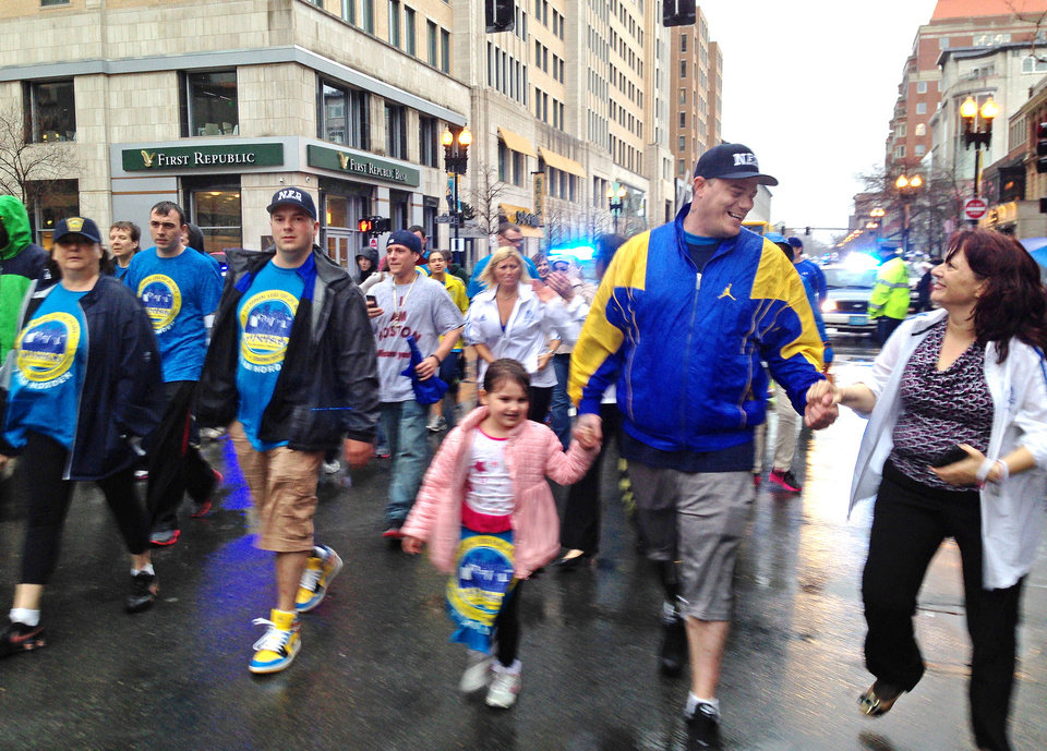 Photo - A woman greets Paul Norden, right, as he and his brother, J.P. Norden, left, walk with a group of family and friends down Boylston Street toward the Boston Marathon finish line in Boston, Tuesday, April 15, 2014. The brothers, each of whom lost his right leg in the 2013 Marathon bombings, traveled the 26.2 miles of the marathon route Tuesday as a fundraiser. They face a lifetime of expenses for the prostheses that have replaced their legs. (AP Photo/Elise Amendola)