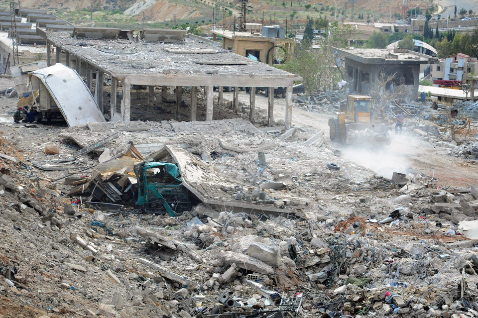Photo - In this photo released by the Syrian official news agency SANA, damaged buildings wrecked by an Israeli airstrike are seen in Damascus, Syria, Sunday, May 5, 2013. Israeli warplanes struck areas in and around the Syrian capital early Sunday, setting off a series of explosions as they targeted a shipment of highly accurate, Iranian-made guided missiles believed to be on their way to Lebanon's Hezbollah militant group, officials and activists said. The attack, the second in three days, signaled a sharp escalation of Israel's involvement in Syria's bloody civil war. Syria's state media reported that Israeli missiles struck a military and scientific research center near the Syrian capital and caused casualties. (AP Photo/SANA)