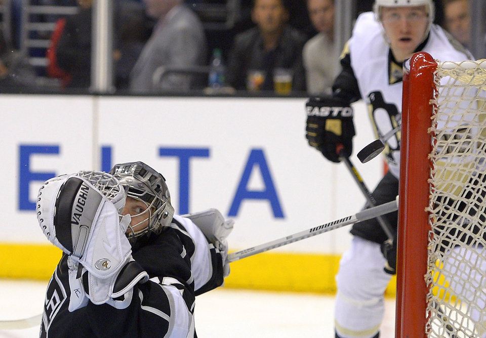 Photo - Los Angeles Kings goalie Jonathan Quick, left, is scored on by Pittsburgh Penguins left wing Chris Kunitz as Penguins left wing Jussi Jokinen, right, of Finland, watches during the first period of an NHL hockey game, Thursday, Jan. 30, 2014, in Los Angeles. (AP Photo)