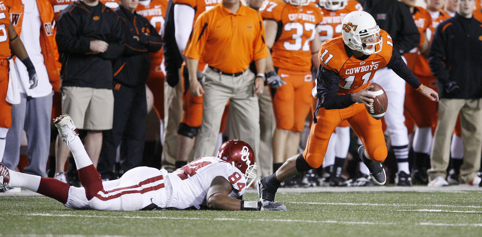 Zac Robinson escapes Frank Alexander during the first half of the college football game between the University of Oklahoma Sooners (OU) and Oklahoma State University Cowboys (OSU) at Boone Pickens Stadium on Saturday, Nov. 29, 2008, in Stillwater, Okla. STAFF PHOTO BY BRYAN TERRY