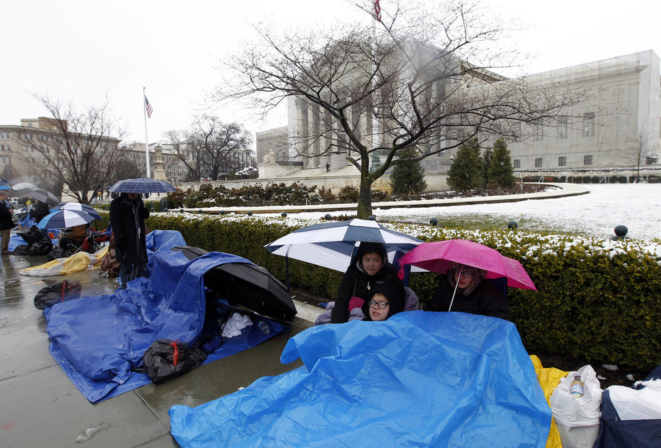 Photo - Taylor, Talla and Vincent Carter cover themselves from the snow as they wait in line outside of the Supreme Court in Washington, Monday March, 25, 2013, to watch Tuesday's same-sex marriage hearing before the Supreme Court. (AP Photo/Jose Luis Magana)