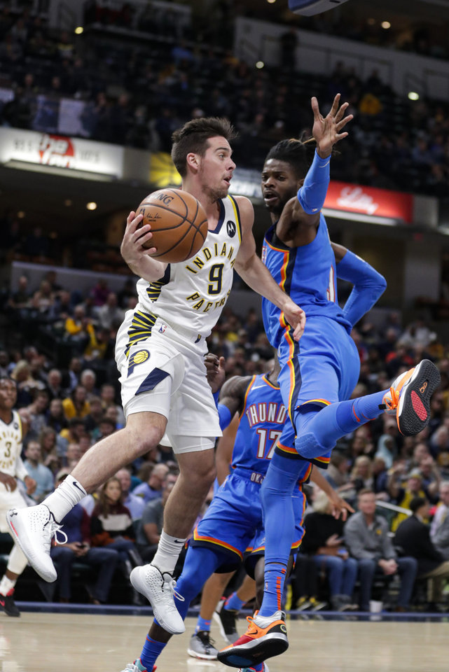 Photo - Indiana Pacers guard T.J. McConnell (9) makes a pass around Oklahoma City Thunder forward Nerlens Noel (9) during the second half of an NBA basketball game in Indianapolis, Tuesday, Nov. 12, 2019. The Pacers won 111-85. (AP Photo/Michael Conroy)