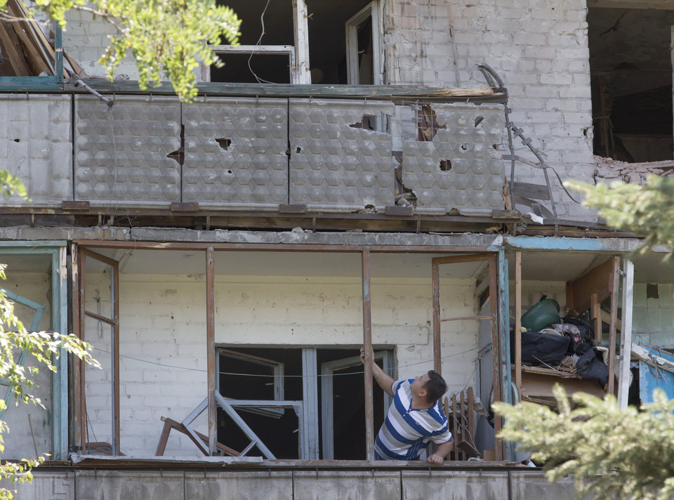 Photo - A man examines damage to his house after shelling in the city of Kramatorsk, Donetsk region, eastern Ukraine, Thursday, July 3, 2014. Residential areas came under shelling on Thursday from government forces. (AP Photo/Dmitry Lovetsky)