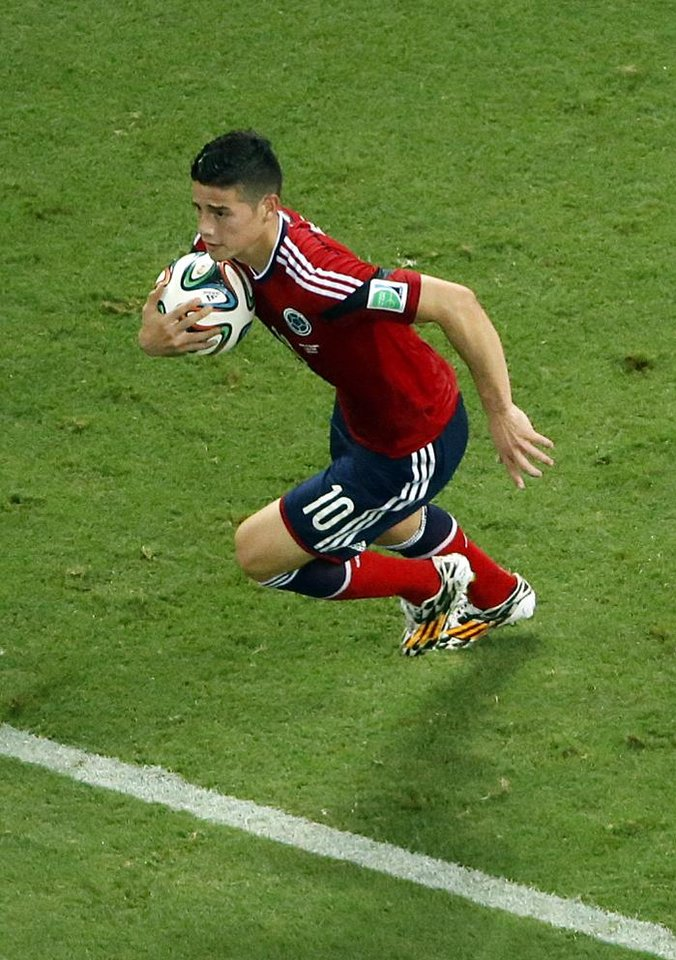 Photo - Colombia's James Rodriguez grabs the ball after scoring on a penalty during the World Cup quarterfinal soccer match between Brazil and Colombia at the Arena Castelao in Fortaleza, Brazil, Friday, July 4, 2014. (AP Photo/Fabrizio Bensch, pool)