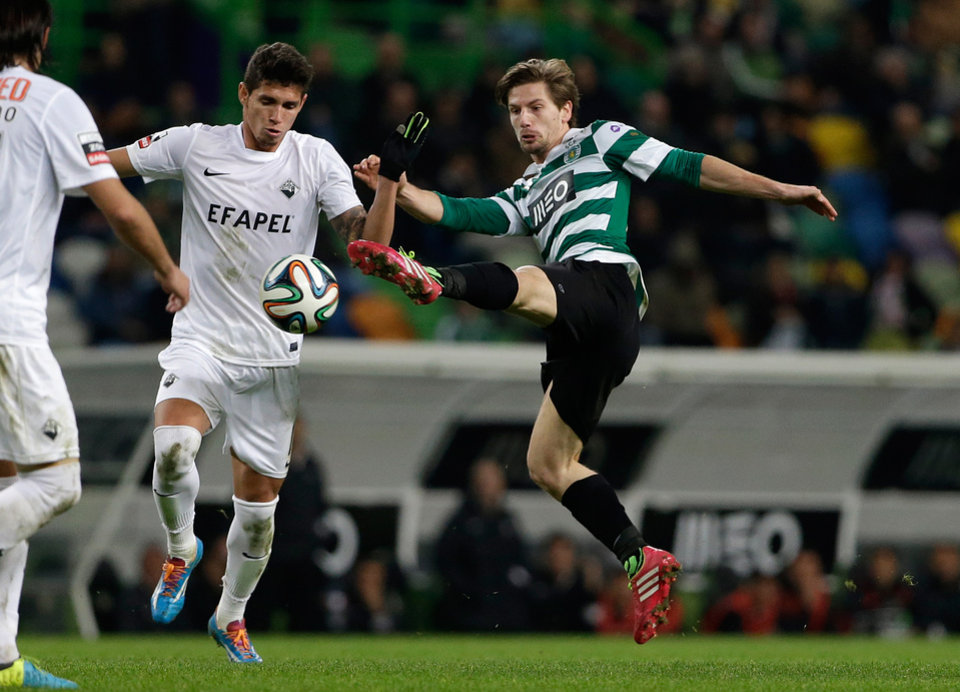 Photo - Sporting's Adrien Silva, right, goes for the ball  during their Portuguese league soccer match with Academica,  Sunday, Feb. 2 2014, at Sporting's Alvalade stadium in Lisbon. (AP Photo/Armando Franca)