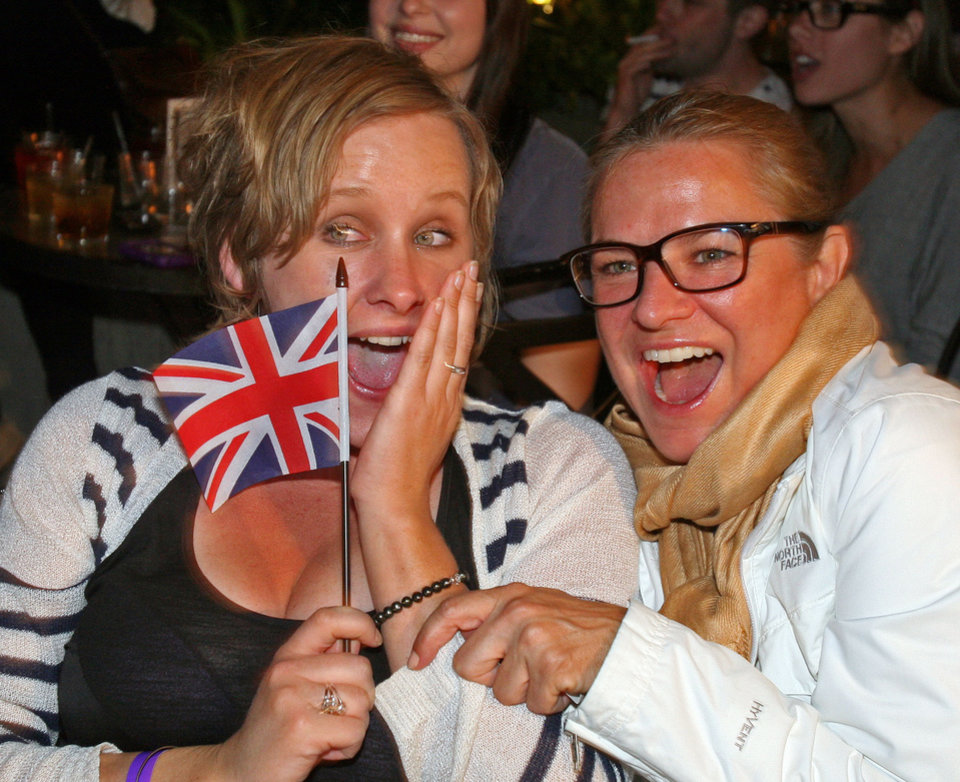 Photo - Patrons Jenny Mueller, left, and Laurin Guthrie watch the royal wedding on television during a