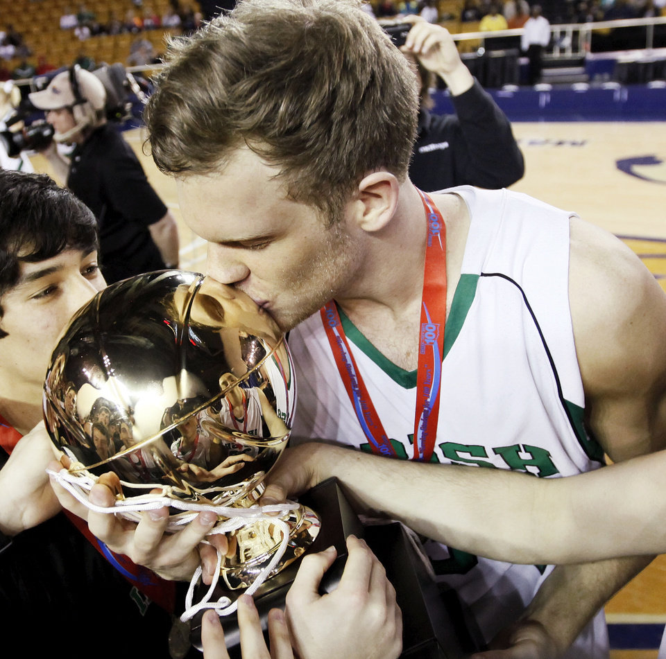 Photo - Matthew Christiansen (34) of Bishop McGuinness kisses the gold ball championship trophy after the Class 5A boys high school basketball state tournament championship game between Bishop McGuinness and East Central at the Mabee Center in Tulsa, Okla., Saturday, March 10, 2012. McGuinness won, 54-41. Photo by Nate Billings, The Oklahoman