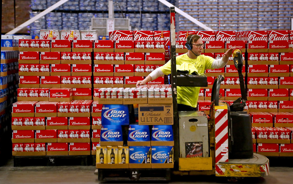 Photo - An employee drives a lift as he pulls orders for shipment in the 100,000 sqf facility at the Anheuser-Busch Sales of Oklahoma (ABSO) distributor on Friday, Jan. 29, 2016, in Oklahoma City, Okla. Photo by Chris Landsberger, The Oklahoman