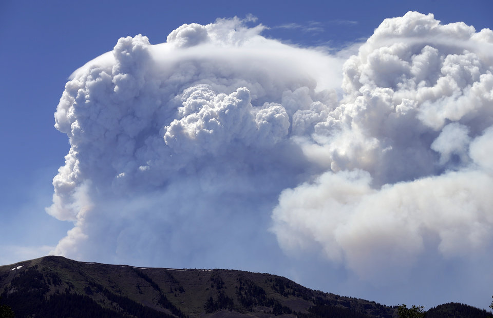 Photo - Wildfire smoke plumes above Del Norte Peak on Sunday, June 23, 2013, in near Del Norte, Colo. A wildfire near a popular summer retreat in southern Colorado continues to be driven by winds and fueled by dead trees in a drought-stricken area, authorities said Sunday. (AP Photo/Gregory Bull)