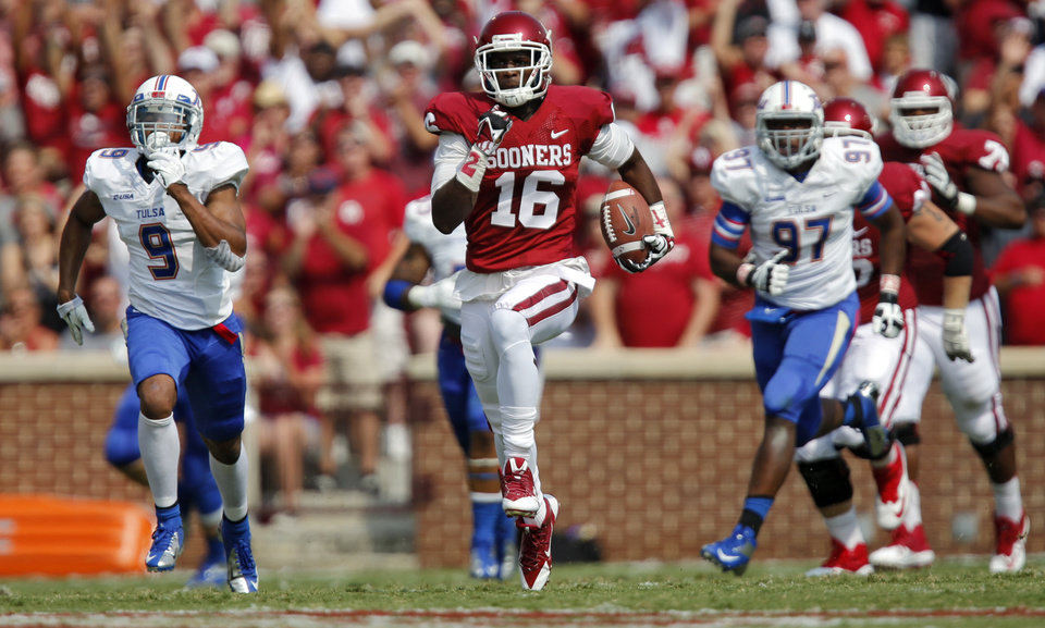 Oklahoma's Jaz Reynolds (16) outruns the defense of Tulsa 's Dwight Dobbins (9) and Brentom Todd (97) during the college football game between the University of Oklahoma Sooners (OU) and the University of Tulsa Hurricanes (TU) at the Gaylord Family-Oklahoma Memorial Stadium on Saturday, Sept. 14, 2013 in Norman, Okla.  Photo by Chris Landsberger, The Oklahoman