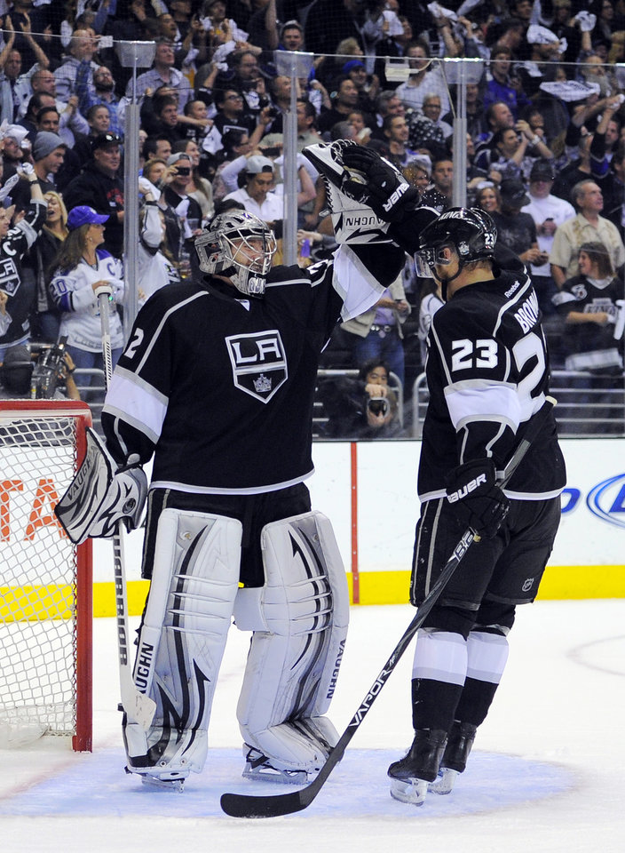 Photo -   Los Angeles Kings goalie Jonathan Quick, left, celebrates with Dustin Brown after the Kings scored an empty-net goal against the St. Louis Blues during the third period in Game 4 of an NHL hockey Stanley Cup second-round playoff series, Sunday, May 6, 2012, in Los Angeles. The Kings won 3-1 to win the series 4-0. (AP Photo/Mark J. Terrill)