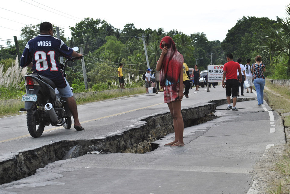 Photo - Residents walk along a damaged road following a 7.2-magnitude earthquake that hit Bohol, central Philippines, Tuesday, Oct. 15, 2013. The tremor collapsed buildings, cracked roads and toppled the bell tower of the Philippines' oldest church Tuesday morning, causing multiple deaths across the central region and sending terrified residents into deadly stampedes. (AP Photo)