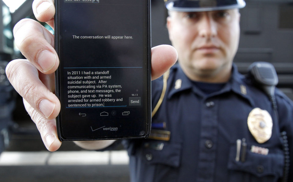 Photo - In a May 6, 2014 photo, Sgt. Andres Wells of the Kalamazoo Deptartment of Public Safety, who successfully used text messaging to negotiate with a suicidal robbery suspect during a 2011 standoff, shows his phone. With 6 billion text messages exchanged daily in the United States, texting is becoming a more frequent part of police crisis negotiations. (AP Photo/Mark Bugnaski)