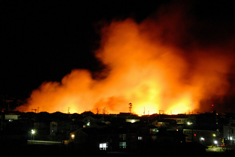 Photo - Fire flames raise from a coastal area after a powerful earthquake in Iwaki city, Fukushima  prefecture (state), Japan, Friday, March 11, 2011. The largest earthquake in Japan's recorded history slammed the eastern coast Friday. (AP Photo/Kyodo News) JAPAN OUT, MANDATORY CREDIT, FOR COMMERCIAL USE ONLY IN NORTH AMERICA ORG XMIT: TTX811