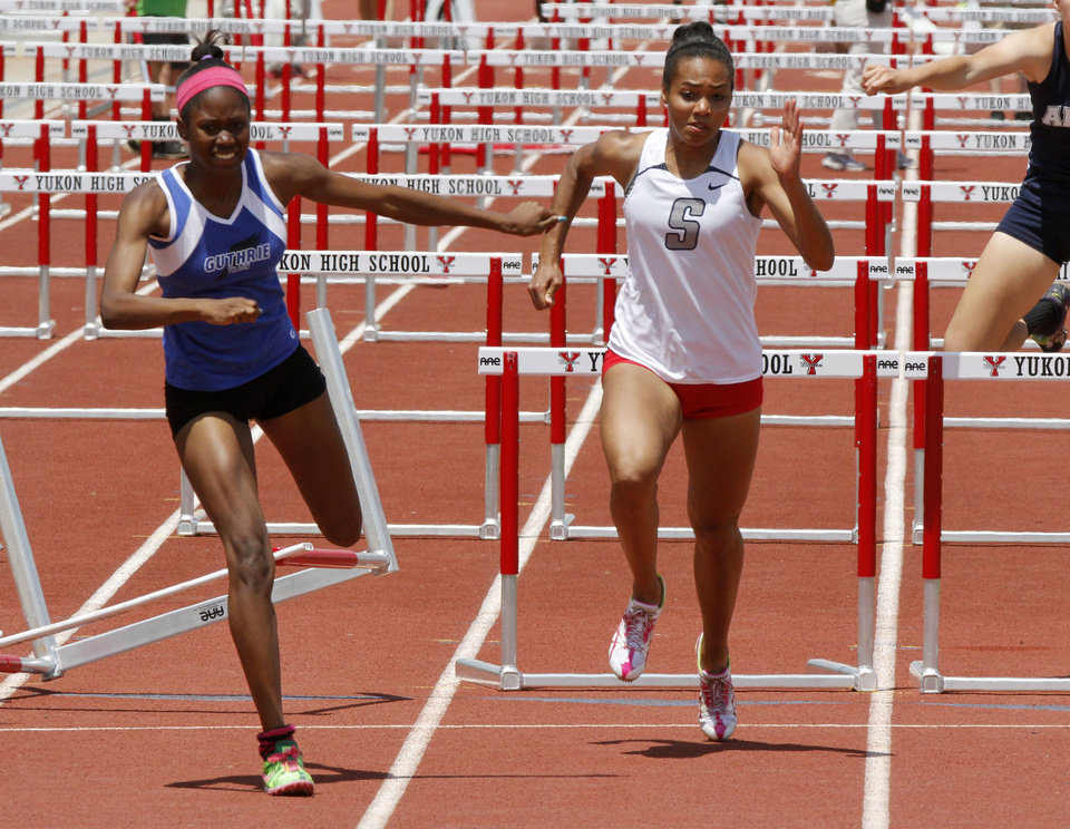 Guthrie's Asia Johnson and Shawnee's Jasmine Robinson run toward the finish line in the girl's 100 meter hurdles of the 5A and 6A State Track Meet in Yukon, OK, Saturday, May 11, 2013,  By Paul Hellstern, The Oklahoman