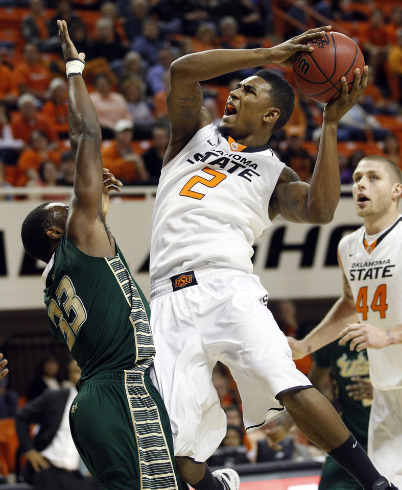 Oklahoma State guard Le'Bryan Nash shoots as South Florida forward Kore White defends in the first half of an NCAA college basketball game in Stillwater, Okla., Wednesday, Dec. 5, 2012. Oklahoma State forward Philip Jurick is at right. (AP Photo/Sue Ogrocki)