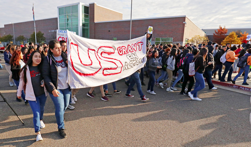 Photo - Students march from the front entry to a courtyard at the school during the DACA support rally at U.S. Grant High School Friday, November 8, 2019. Photo by Doug Hoke