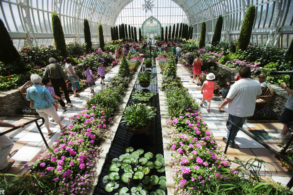 Photo - In this photo taken Tuesday, June 3, 2014, visitors walk through the glassed-in Conservatory which shows off tropical and other exotic plants year round in a variety of indoor and outdoor gardens in St. Paul, Minn. (AP Photo/Jim Mone)