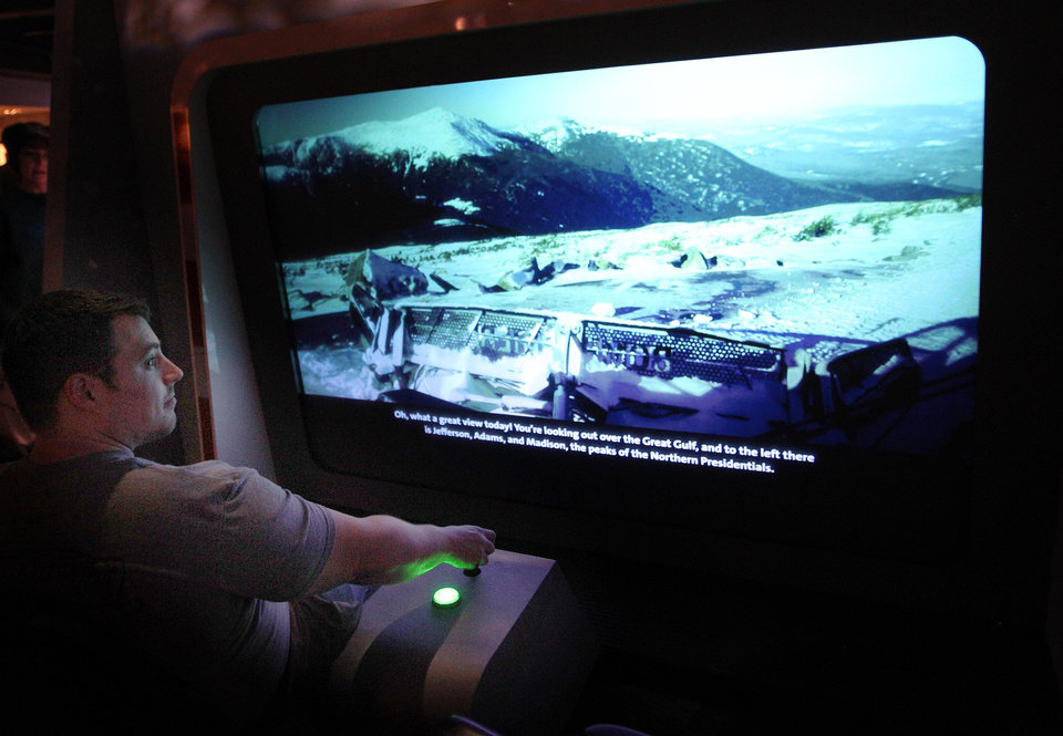 In this Monday June 16, 2014 photo, a simulator of a snowcat driving up the Mount Washington Auto road is used at the new Extreme Museum on the top of Mount Washington. The new Extreme Mount Washington museum recently underwent a $1 million transformation from a modest collection of artifacts behind glass to a modern facility packed with hands-on exhibits.(AP Photo/Jim Cole)