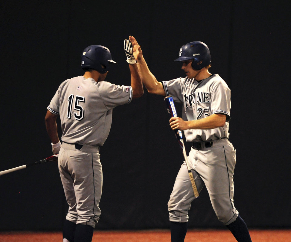 Photo - UC Irvine's Garrett Williams, left, congratulates teammate Trey Cobb after he scores a run against Oklahoma State during the fifth inning an NCAA college baseball super regional tournament game in Stillwater, Okla, Friday, June 6, 2014. (AP Photo/Brody Schmidt)