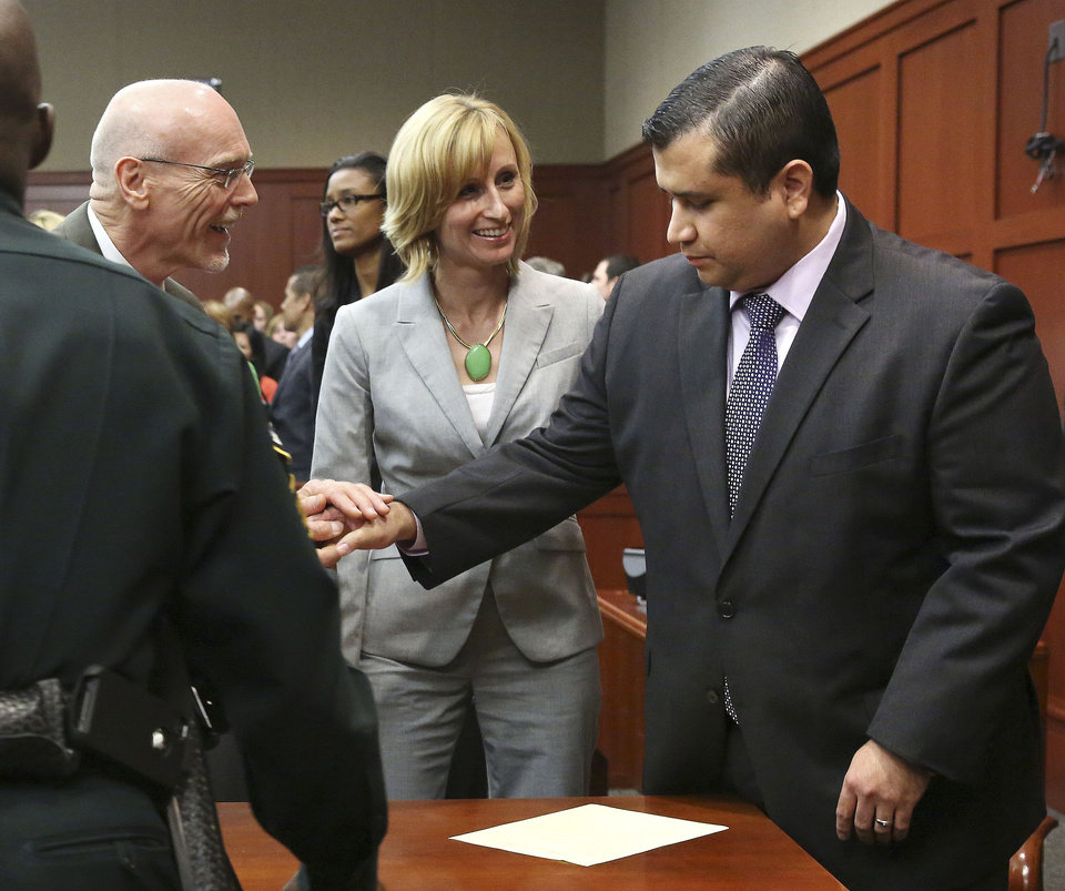 Photo - George Zimmerman, right, is congratulated by his defense team after being found not guilty during  Zimmerman's trial in Seminole Circuit Court in Sanford, Fla. on Saturday, July 13, 2013. Jurors found Zimmerman not guilty of second-degree murder in the fatal shooting of 17-year-old Trayvon Martin in Sanford, Fla. The six-member, all-woman jury deliberated for more than 15 hours over two days before reaching their decision Saturday night. (AP Photo/Gary W. Green, Pool) ORG XMIT: FLJR402