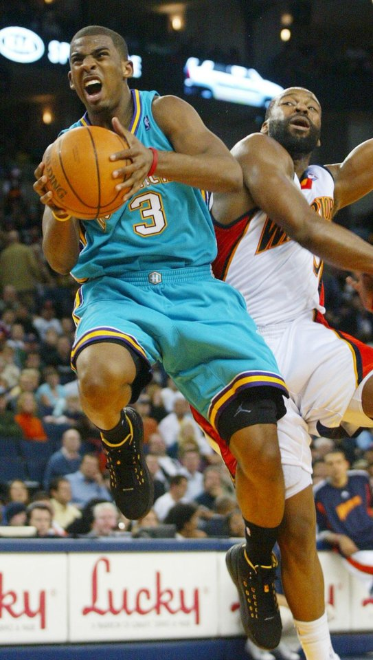 Photo - New Orleans Hornets' Chris Paul rebounds ahead of Golden State Warriors Baron Davis in the second half of an NBA basketball game, Friday, Jan. 4, 2008 in Oakland, Calif. The Hornets beat the Warriors. (AP Photo/George Nikitin) ORG XMIT: CAGN108