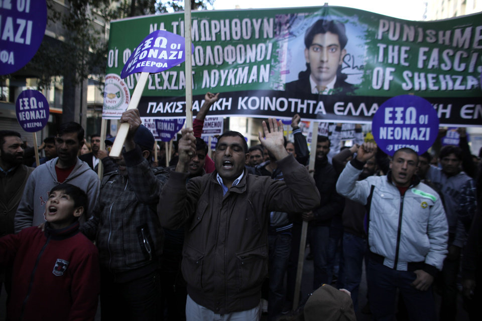 Mourners holding a banner  with the photo of  Shehzad Luqman, a Pakistani immigrant who was murdered on Thursday after being stabbed by suspected extreme rightists, shout slogans during a protest in Athens on Saturday, Jan. 19 2013. An estimated 3,000 people marched  through central Athens in protest at a spate of anti-immigrant attacks that turned fatal Thursday when a 27-year-old Pakistani immigrant was stabbed by suspected extreme rightists.  (AP Photo/Kostas Tsironis)