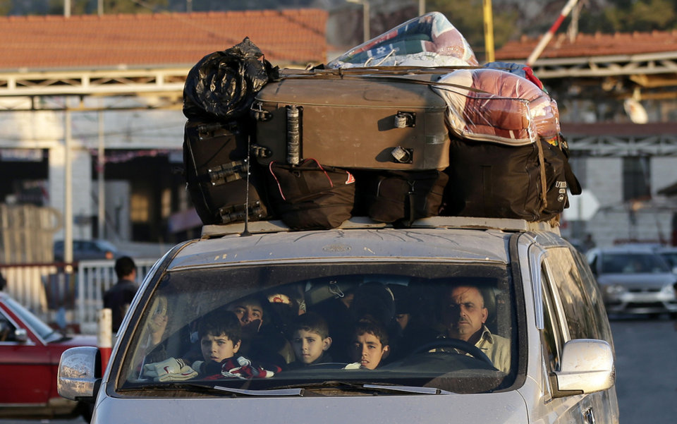 A Syrian family crosses into Lebanon at the border crossing in Masnaa, eastern Lebanon, Friday, Nov. 30, 2012. Syrian rebels battled regime troops south of Damascus on Friday and Internet and most telephone lines were cut for a second day, but the government reopened the road to the capital's airport in a sign the fighting could be calming, activists said. (AP Photo/Hassan Ammar)