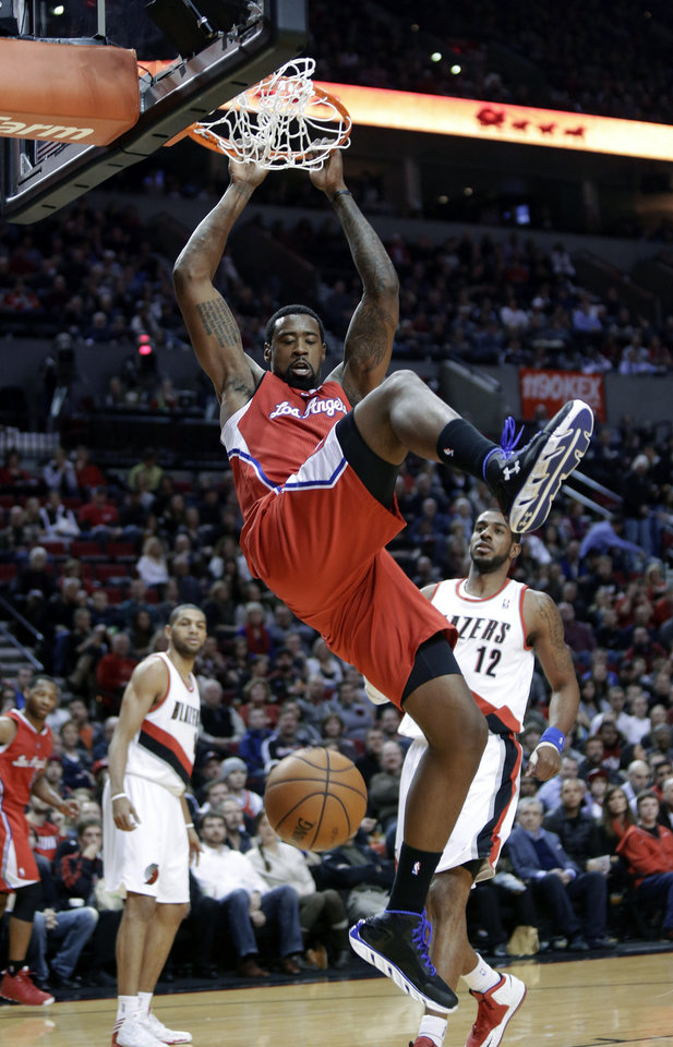 Los Angeles Clippers center DeAndre Jordan, middle, scores against the Portland Trail Blazers' LaMarcus Aldridge, right, and Nicolas Batum, left, during the first quarter of an NBA basketball game in Portland, Ore., Saturday, Jan. 26, 2013.(AP Photo/Don Ryan)