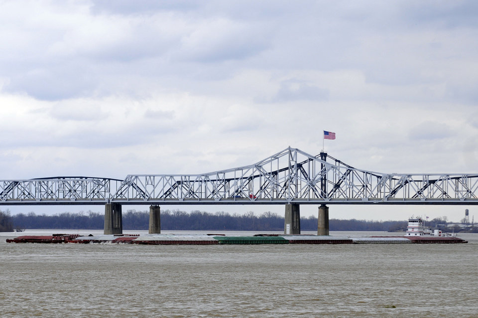 The towboat Harold B. Dodd pilots south on the Mississippi River as vehicles cross the Interstate 20 bridge in Vicksburg, Miss., Wednesday, Jan. 30, 2013. Commercial traffic for southbound vessels on the Mississippi River resumed Wednesday after closing Sunday. (AP Photo/Vicksburg Post, Eli Baylis)