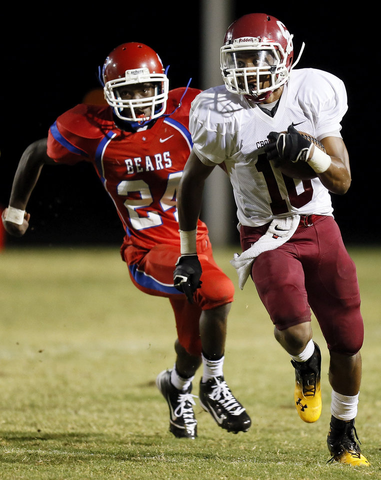 Photo - Crooked Oak's Sanardo Ballard (10) runs away from John Marshall's Rayquan Chatman (24) during a high school football game between John Marshall and Crooked Oak at Star Spencer's Carl Twidwell Stadium, 3001 NE Spencer Rd., in Spencer, Okla., Thursday, Sept. 19, 2013. Photo by Nate Billings, The Oklahoman