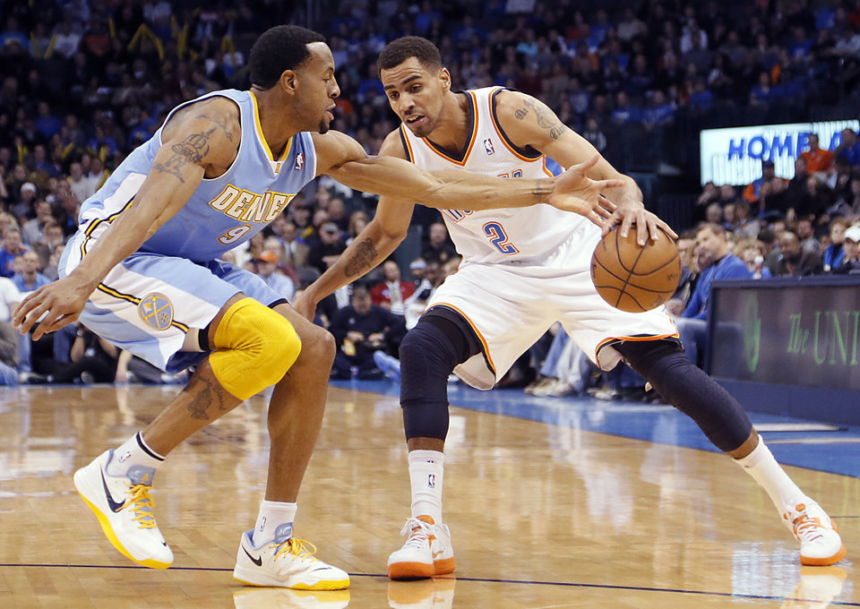 Oklahoma City's Thabo Sefolosha (2) drives past Denver's Andre Iguodala (9) during the NBA basketball game between the Oklahoma City Thunder and the Denver Nuggets at the Chesapeake Energy Arena on Wednesday, Jan. 16, 2013, in Oklahoma City, Okla.  Photo by Chris Landsberger, The Oklahoman